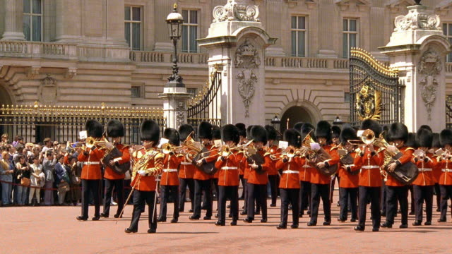 wide shot royal guard playing instruments and marching in forecourt of buckingham palace / london - marching stock videos and b-roll footage