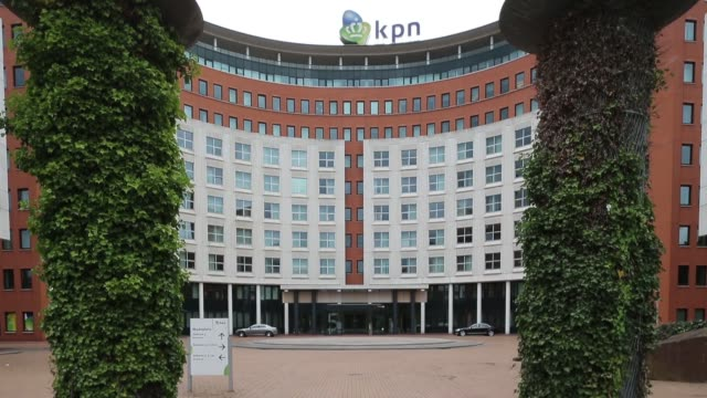 Wide shot Royal KPN NV headquarters in The Hague Netherlands on Monday Sept 9 Pedestrians walk in the rain past a KPN mobile phone store operated by...
