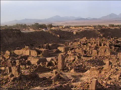 stockvideo's en b-roll-footage met wide shot ruins of buildings in bam w/mountains in background after earthquake / iran / - 2003