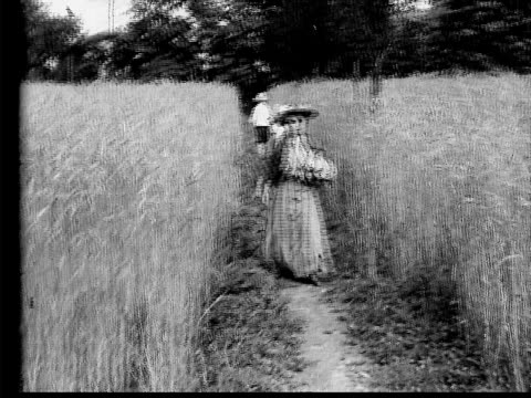 1910 B/W Wide shot sad woman walking toward camera down path in field of wheat as boy and girl walk the other way