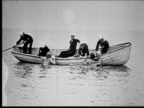 1914 B/W Wide shot Sailors in rowboat rescuing man and woman swimming in sea