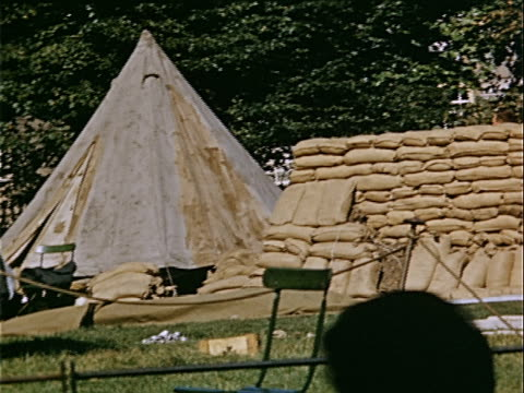 wide shot sandbags piled in heap outside british military tent during war preparations / london, england - british military stock videos & royalty-free footage