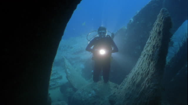wide shot scuba diver holding light near shipwreck underwater - shipwreck stock videos & royalty-free footage