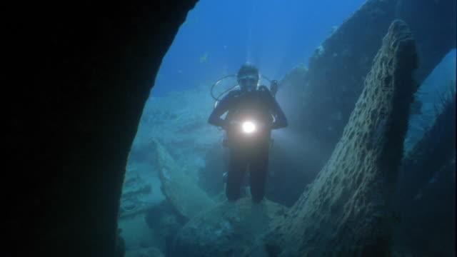 stockvideo's en b-roll-footage met wide shot scuba diver holding light near shipwreck underwater - scheepswrak