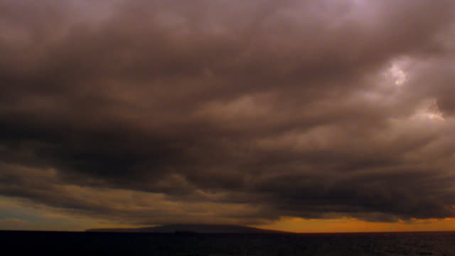 Wide shot sea of time lapse storm clouds over silhouetted horizon at sunset / Hawaii