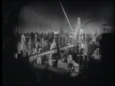 B/W 1940 wide shot searchlights over futuristic city at night