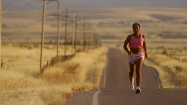 vidéos et rushes de wide shot selective focus black woman jogging on remote road in desert / arizona - route à une voie