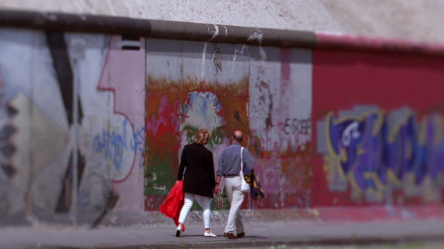 Wide shot selective focus couple walking past painted section of Berlin Wall / Germany