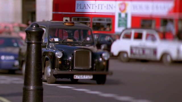 Wide shot selective focus pan rack focus taxi and car driving on road with double decker stopped in traffic / London