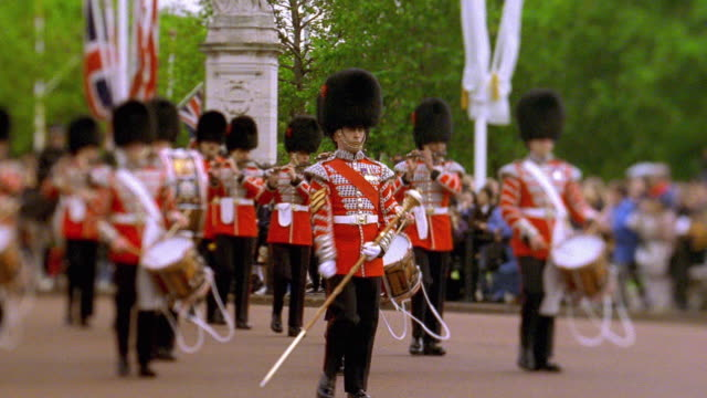 wide shot selective focus pan royal guard band marching at buckingham palace / crowd in background / london - 近衛兵点の映像素材/bロール