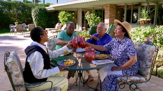 wide shot senior black couple and senior hispanic couple toasting, sitting at patio table outdoors / arizona - アイスティー点の映像素材/bロール