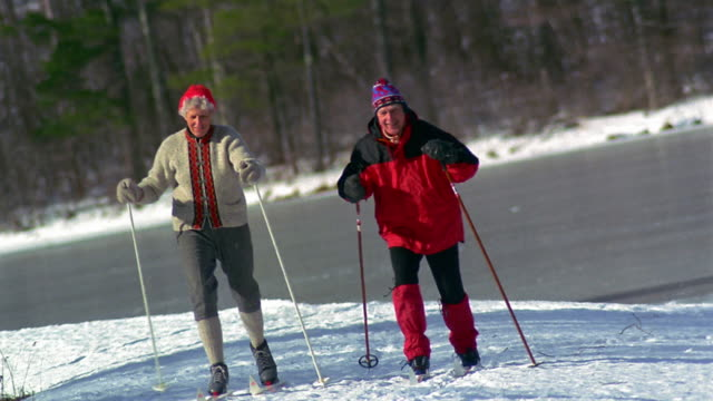 canted wide shot pan senior couple cross country skiing / vermont - vermont stock-videos und b-roll-filmmaterial