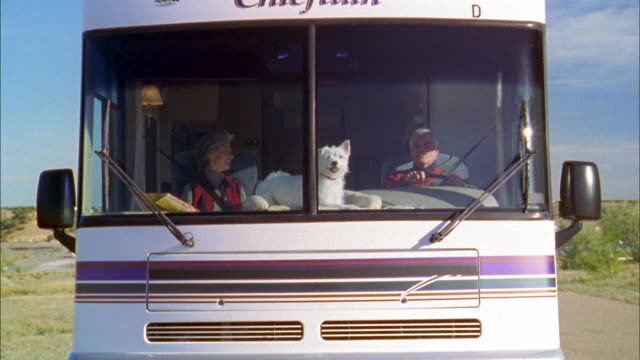 wide shot senior couple driving in motor home w/dog in front window - camper van stock videos & royalty-free footage