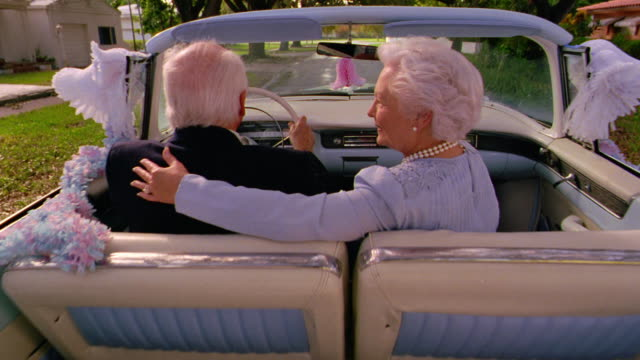 "REAR VIEW wide shot senior couple kissing in convertible / man drives away revealing ""Just Married"" sign"