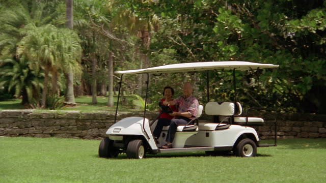 wide shot senior couple riding in golf cart and smiling - golf cart stock videos and b-roll footage