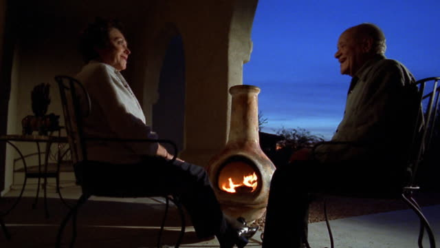 wide shot senior couple sitting by fire of outdoor fireplace - falling in love stock videos and b-roll footage