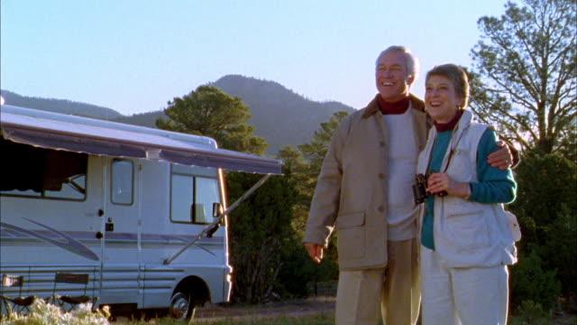 vídeos de stock, filmes e b-roll de wide shot senior couple smiling and looking through binoculars w/motor home in background - de braços dados
