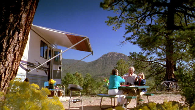 wide shot senior couple w/granddaughter sitting at picnic table outside motor home / mountain in background - wohnmobil stock-videos und b-roll-filmmaterial