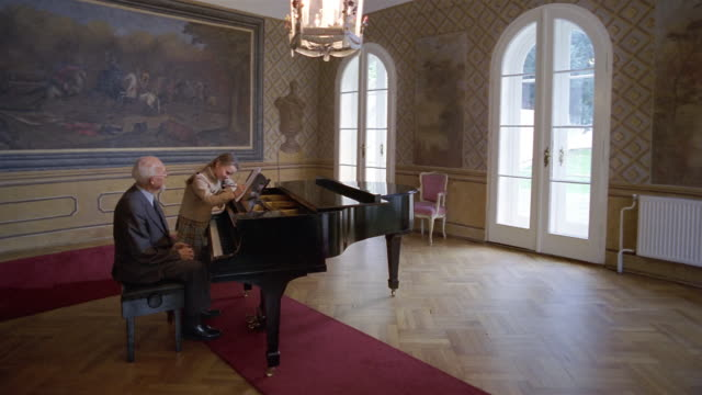 Wide shot senior man giving piano lesson to young girl in room with oil painting and French doors