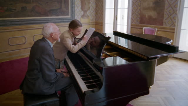 Wide shot senior man playing notes on piano and young girl taking notation on sheet music during piano lesson