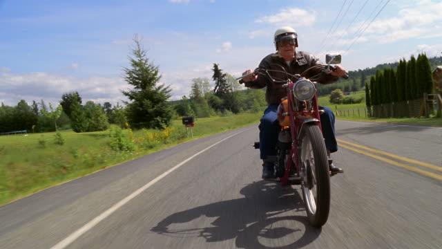 vídeos de stock e filmes b-roll de wide shot senior man riding motorcycle on country road / washington, usa - capacete moto