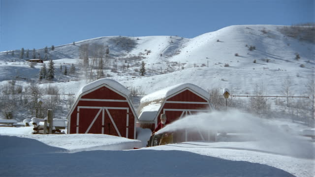 Wide shot senior man snowblowing in front of barn / Jackson Hole, Wyoming