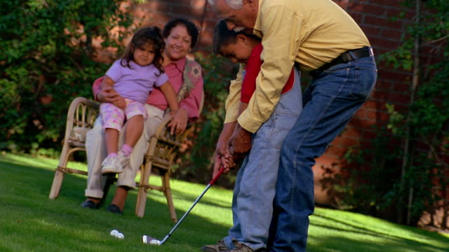 wide shot senior man teaching young boy how to swing golf club with young girl on senior woman's lap in background - putting stock videos & royalty-free footage