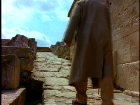 1996 Wide shot Senior man with cane walking up stone path at Knossos ruins/ Crete, Greece