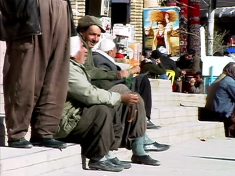 wide shot senior men holding prayer beads and sitting on steps along sidewalk/ turkey - prayer beads stock videos & royalty-free footage