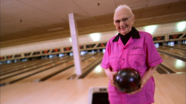 wide shot senior woman in pink jersey with'dottie' nametag holding bowling ball and smiling at cam - shirt stock videos & royalty-free footage