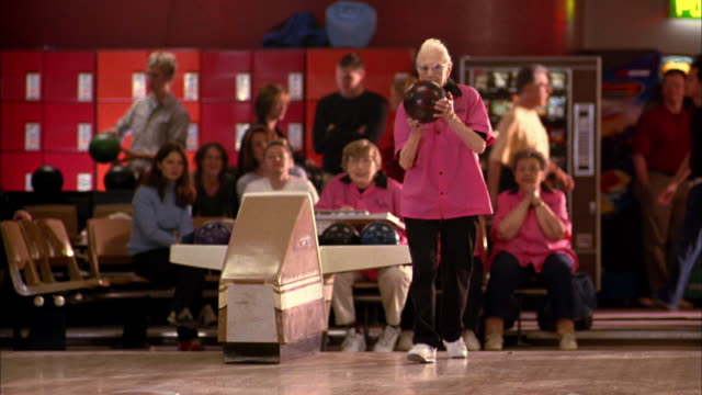 wide shot senior woman in 'pink ladies' team jersey bowling and waving off shot - ten pin bowling stock videos & royalty-free footage
