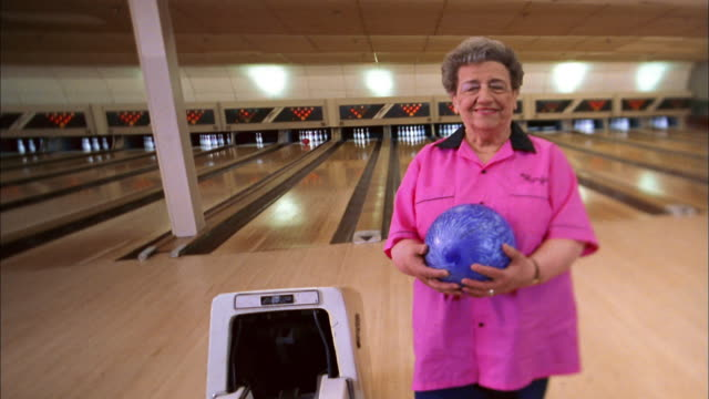 wide shot senior woman in pink team jersey holding bowling ball and smiling at cam - pink shirt stock videos and b-roll footage