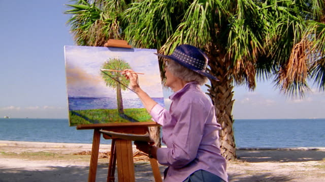 wide shot senior woman painting painting picture of palm tree on beach - staffelei stock-videos und b-roll-filmmaterial
