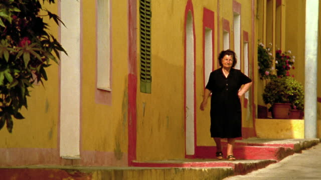 wide shot senior woman walking down stairs next to yellow building / linosa, sicily - italian culture stock videos & royalty-free footage
