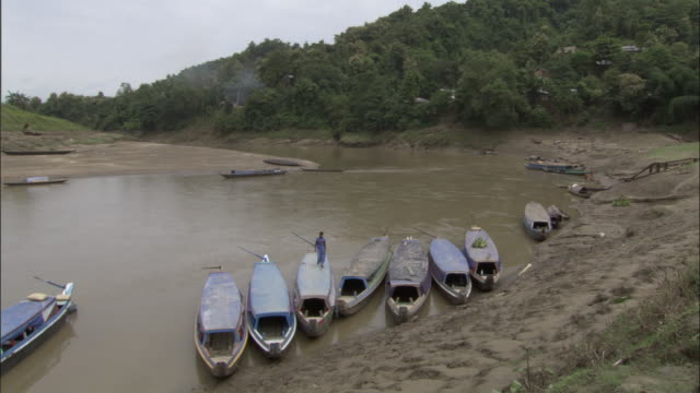 wide shot - several boats wading near a muddy shore / bangladesh  - 雨林点の映像素材/bロール