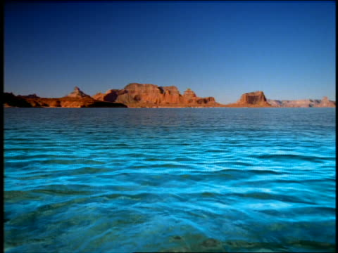 stockvideo's en b-roll-footage met wide shot shallow lake water with rock formations in background / lake powell, utah - powellmeer