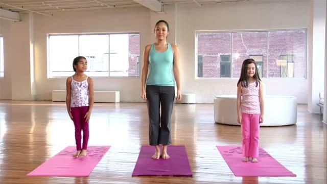 vídeos y material grabado en eventos de stock de wide shot shot mother and two girls doing yoga in loft/ brooklyn, new york - vriksha asana