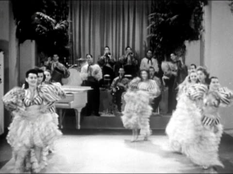 1941 wide shot showgirls in ruffled skirts dancing with latin big band playing in background/ audio - maraca stock videos & royalty-free footage