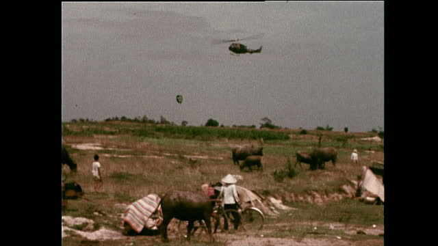 wide shot showing a large military helicopter flying above the refugee camp set up by displaced villagers from my thanh; vietnam, 1972. - non us film location stock videos & royalty-free footage