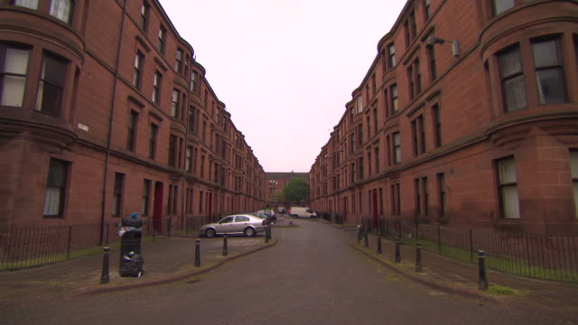 wide shot showing a symmetrical view of victorian tenement buildings in glasgow's govan area, scotland. - 固定された点の映像素材/bロール