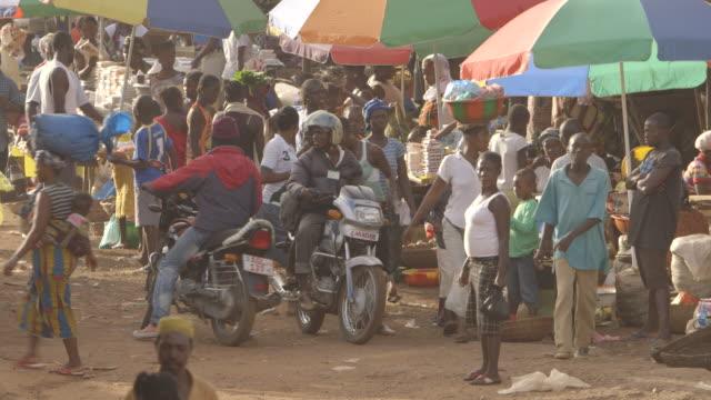 Wide shot showing okada motorcycle taxis on a busy street running through a market in Kenema, Sierra Leone.