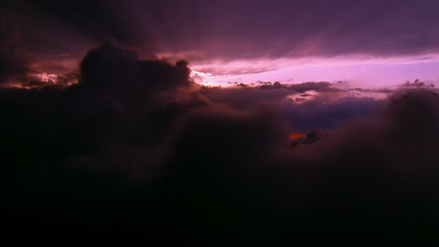 wide shot side aerial point of view through clouds with sunset and god rays in background - aircraft point of view stock videos & royalty-free footage