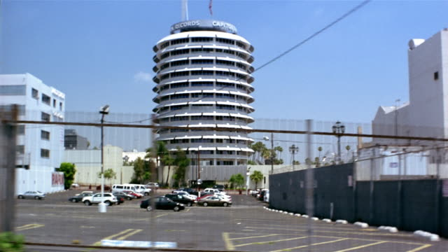 Wide shot side car point of view driving past Capitol Records building / Hollywood, California