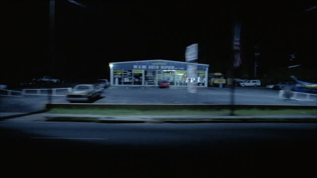 wide shot side car point of view driving past restaurant, auto repair shop and gas station at night - parking stock videos & royalty-free footage
