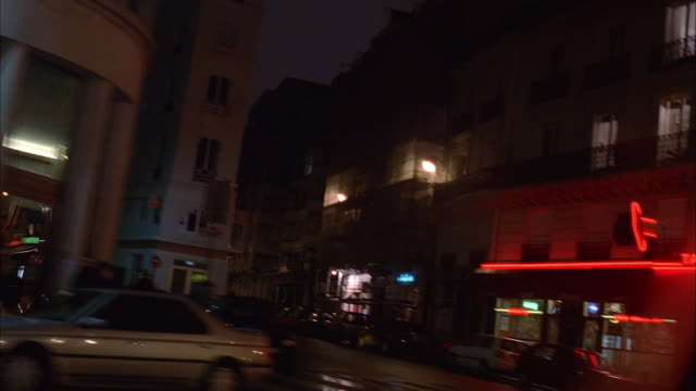 vidéos et rushes de wide shot side car point of view driving past restaurants, bars, stores and parked cars on street at night / paris - signalisation