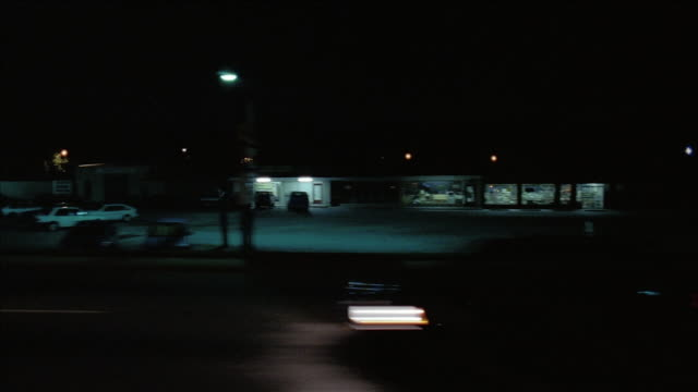 wide shot side car point of view driving past stores and strip malls at night - moving process plate stock videos & royalty-free footage