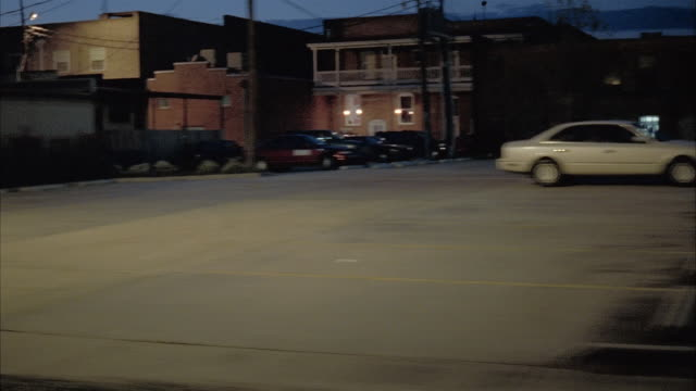 wide shot side car point of view traveling past storefronts on small town street at twilight / louisiana - petrol station stock videos & royalty-free footage