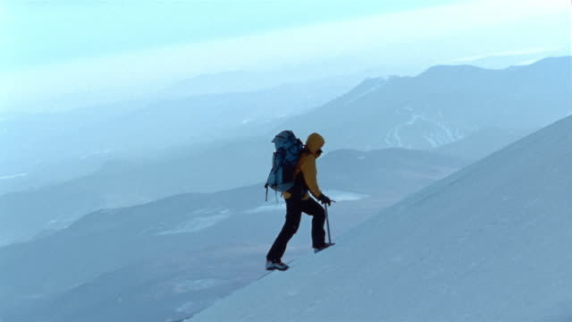stockvideo's en b-roll-footage met wide shot side view of mountain climber hiking up mount washington / carrying ice pick / new hampshire - new hampshire
