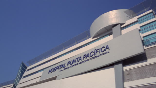 wide shot sign hanging outside hospital punta pacifica/ panama city, panama  - スウィッシュパン点の映像素材/bロール