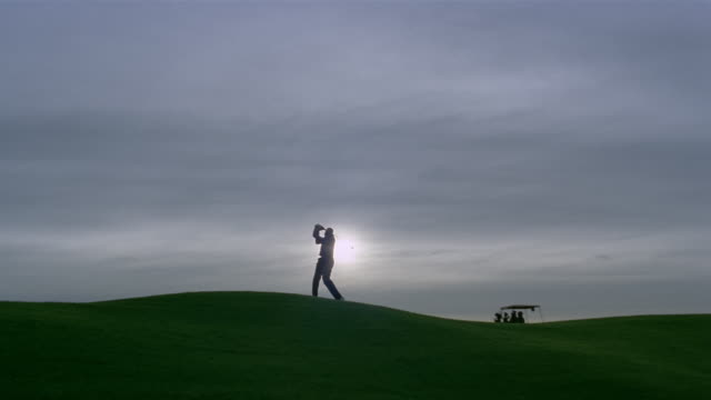 wide shot silhouette of man golfing on hill as golf cart passes in background/ phoenix, arizona - golf swing silhouette stock videos & royalty-free footage